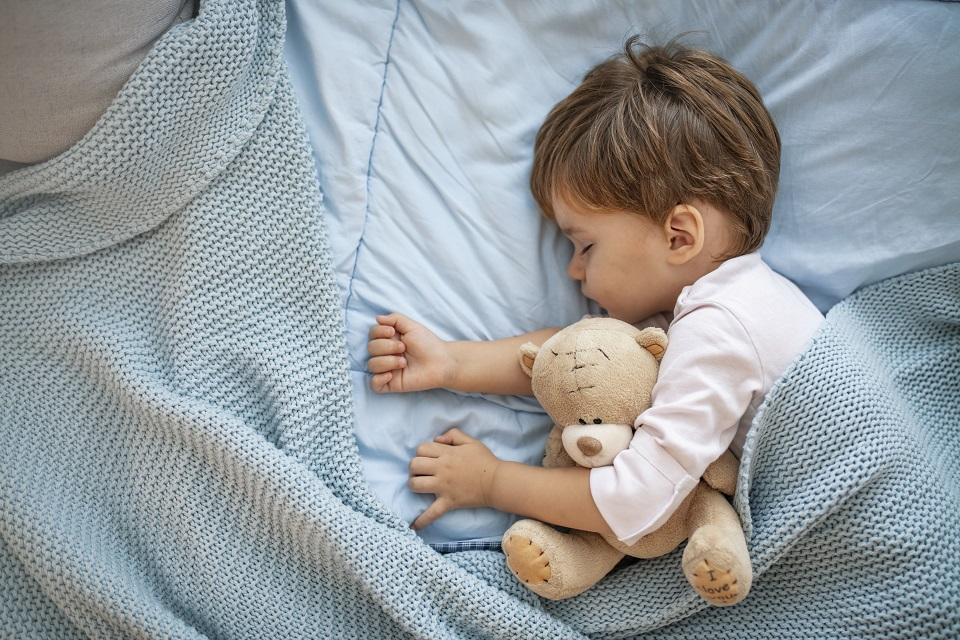 Cute little boy sleeping in bed at home. Sleeping baby in bed, holding a teddy bear. Sweet dreams. Little baby boy sleeping while lying on couch at home. Boy sleeping on bed with teddy bear